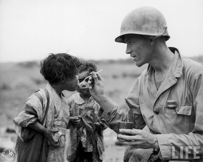 American Army Lt. Richard K. Jones sharing his food rations w. pair of young Japanese children found hiding in an abandoned tomb.