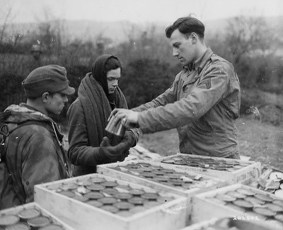 U.S.Army corporal handing out C rations to German prisoners